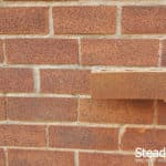 Brick tinted with burnt orange and flecked with coffee brown and carbon black against original bricks