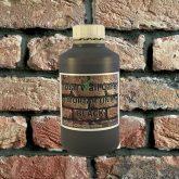 Bottle of Black Mortar Tint against brick wall