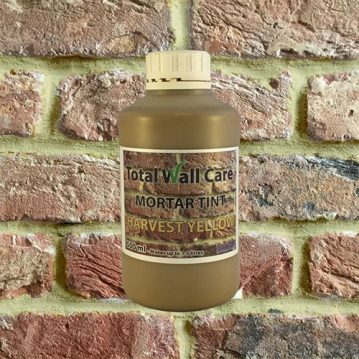 Bottle of Harvest Yellow Mortar Tint against brick wall