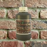 Bottle of Khaki Mortar Tint against brick wall