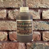 Bottle of Plum Mortar Tint against brick wall
